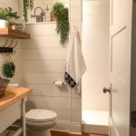 Bathroom With Wooden Floor, White Wall Plank, White Vanity Table With Wooden Top, White Toilet, Wooden Floating Shelves, Plants, Wall Accessories