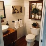 Bathroom, Wooden Floor, White Wall Planks, White Toilet, Wooden Vanity Table, White Sink, Black Towel Handler, Glass Door Cabinet, Mirror, Sconces