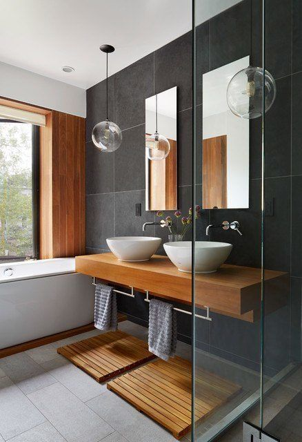bathroom, wooden vanity with white sink, towel handler under, wooden footing, grey tub, wooden wall, black tiles backsplash, clear bulbs pendants