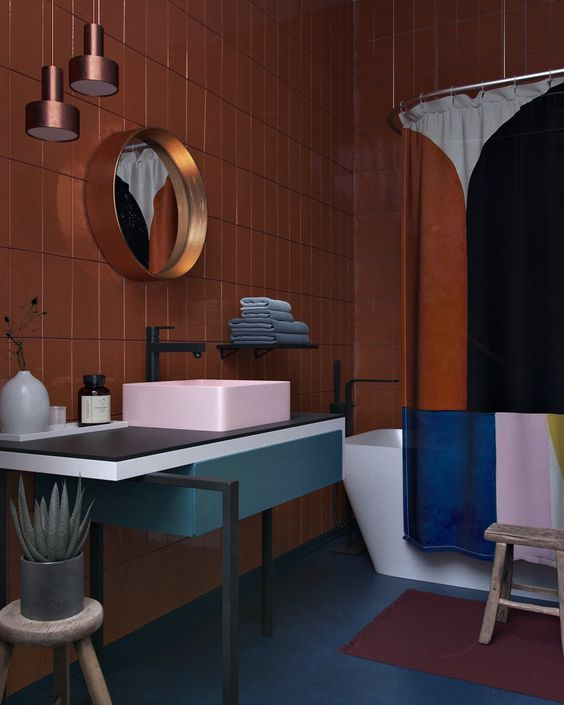 bathroom, yellow wall tiles, blue seamless floor, blue black asymmetric vanity table with pink sink, golden framed mirror, copper pendant, white tub, colorful curtain