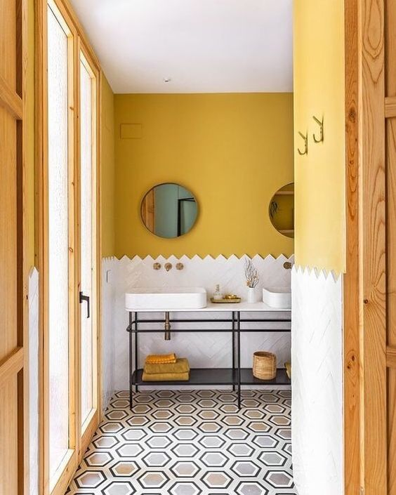 bathroom, yellow wall, whtie tiles wainscoting, black metal vanity tables, white top, white sinks, hexagonal tiles