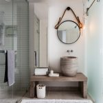 Beachy Bathroom Round Wall Mirror Glass Shower Door Towel Holder White Bathroom Rug Limestone Floor Wooden Bench Sink Bowl Mirrored Cabinet Frosted Glass Sliding Door