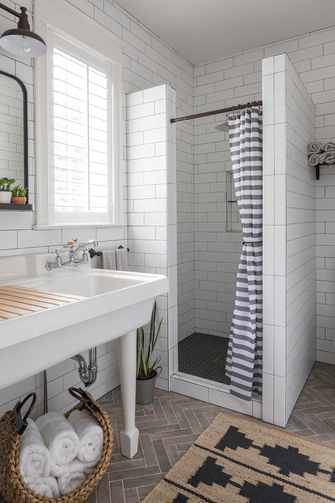 beachy bathroom white subway wall tile grey and white stripe shower curtain herringbone floor tile traditional rug white sink rattan towel basket window mirror