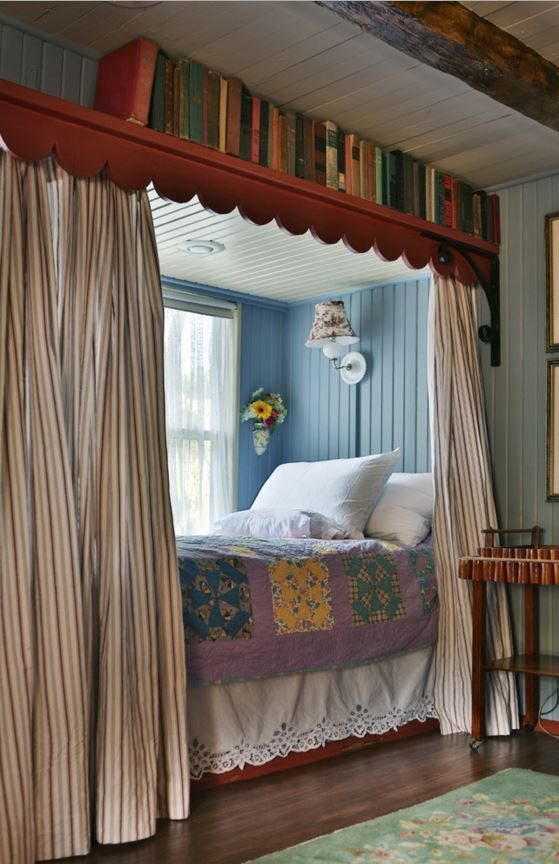 bed nook, blue wooden wall, white wooden ceiling, white bedding, striped curtain, bookshelves on top of the curtain, sconces