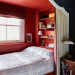 Bed Nook, Red Inside Wall With Shelves On Headboard, Window With Red Shade, White Red Curtain, Black Painted Wall Outside, White Framed Curvy Arch