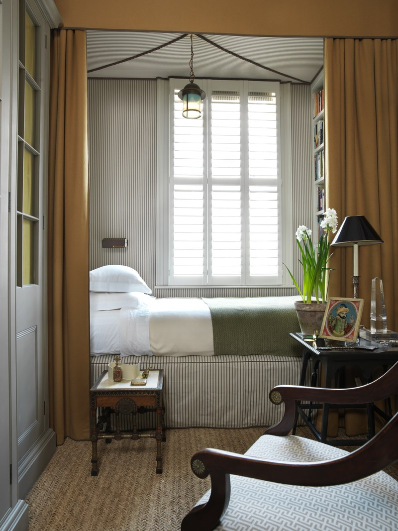 bed nook, striped bed platform cover, brown curtain, bookshelves on the side wall, window, pendant