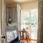 Bed Nook, Wooden Floor, Blue Rug, Blue White Bedding, Blue Pattern Curtain On Rail, White Wall, Glass Door