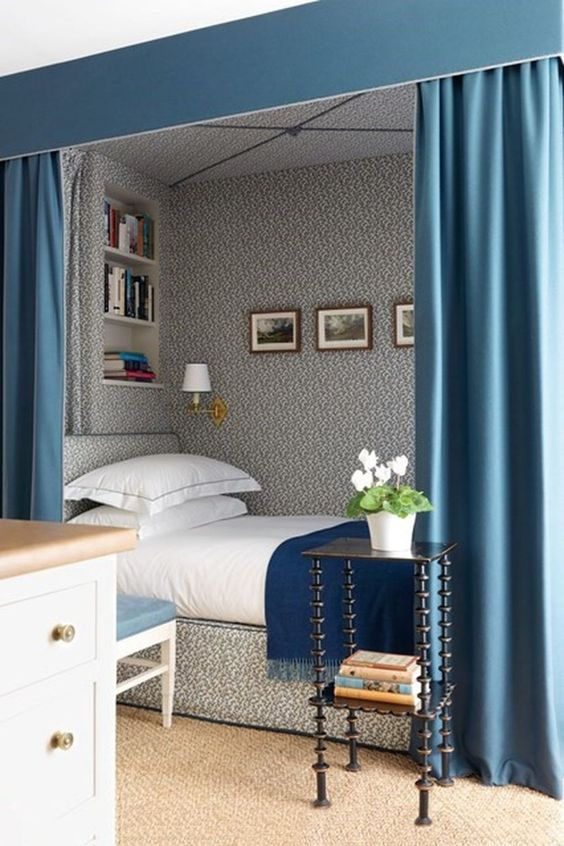 bedding nook with grey wallpaper, grey bed platform, green curtain, white bedding, shelves on the headboard, sconce, wall pictures