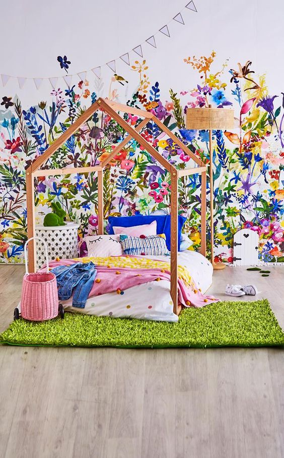 bedroom with wooden floor, faux grass rug, wooden bed platform, colorful flower wallpaper