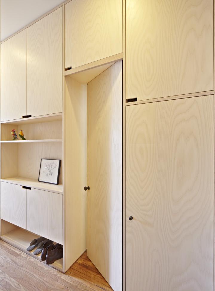 bedroom, wooden floor, built in cabinet, desk, and shelves, door