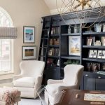Black Bookcase On The Wall With Stairs, Beige Wall, White Chair, Rug, Study Table, Acrylic Chair, Pendant