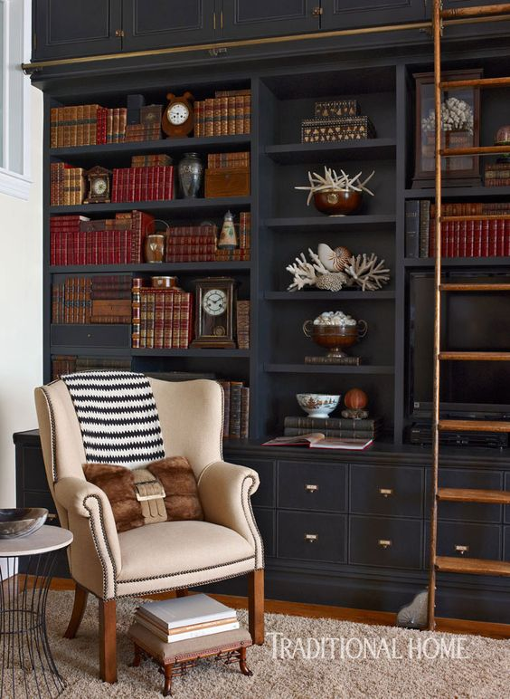 black bookcase with brown sliding stairs, beige leather chair, round side table, rug