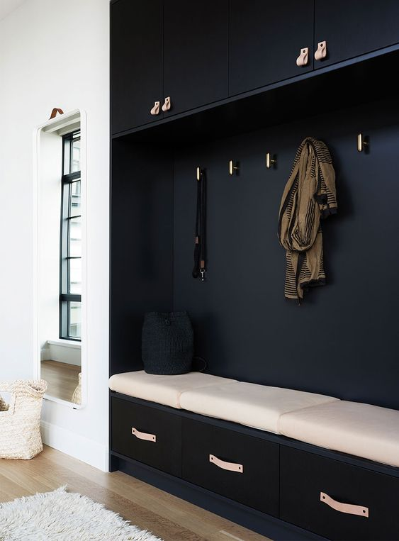 black cupboard with large seating nook, drawers at the bottom, white cushion, golden hooks on the nook