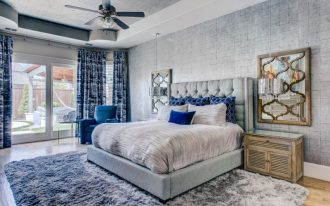 blue and gray bedroom grey wallpaper grey shag rug blue curtains grey bed grey bedding blue pillows wall mirror traditional nightstand blue armchair ceiling fan with lamp