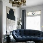 Blue Tufted Curvy Sofa, Ottoman, Wooden Floor, Pendant, White Wall, Window