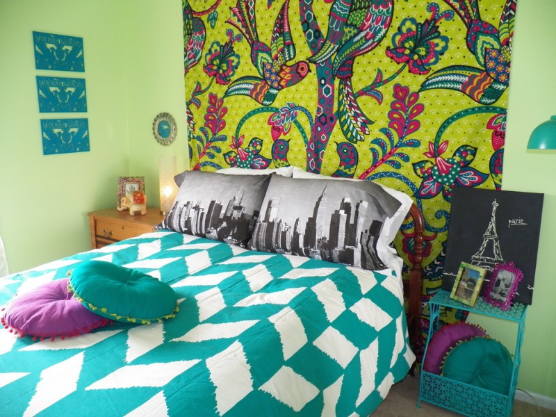 bohemian duvet cover colorful wall decor wooden and plastic nightstands table lamp frames green white bedding pillows green walls