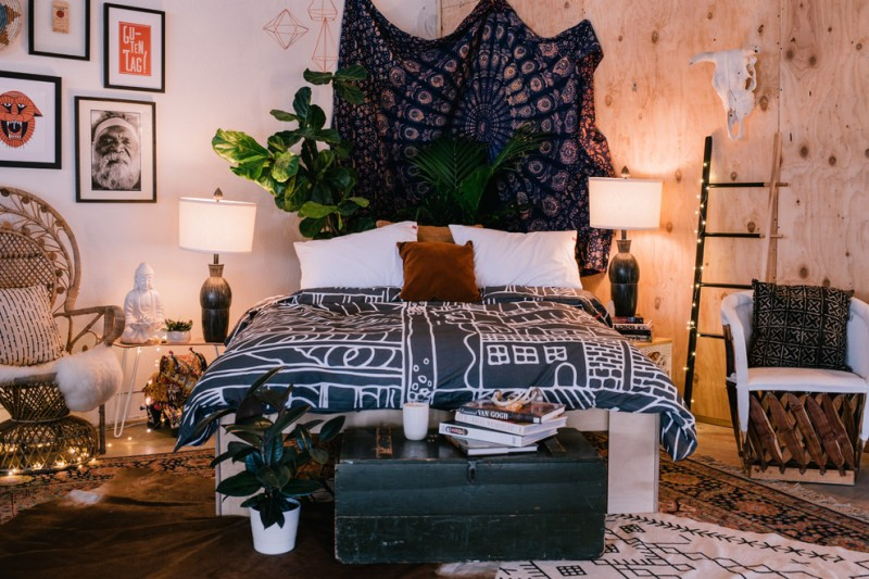 bohemian duvet cover wooden and white walls plants tapestry table lamps nightstands mediterranean rugs black trunk rattan chairs ladder