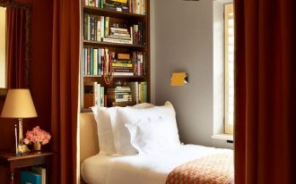 bookworm bed along the window, white bedding, red bed platform, red curtain, grey wall, wooden shelves on the wall, red curtain