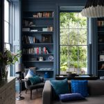 Built In Shelves On The Sides Of Windows In Dark Blue, Grey Chairs, Black Coffee Table, Wooden Floor