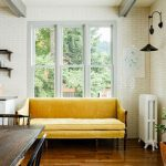 Classic Minimalist Yellow Sofa, Wooden Floor, White Subway Wall, Wooden Dining Set, Sconces, Open Floating Shelves