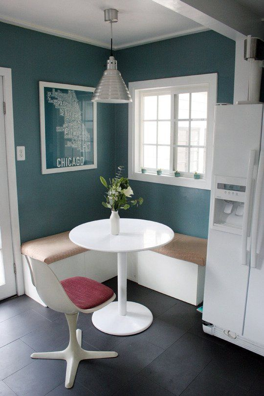 corner dining nook, white bench with brown cushion, white roun table, white chair with red seating, green wall, silver pendant, window