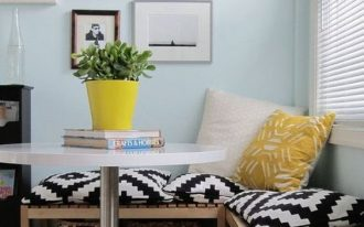 corner dining nook, wooden corner bench with shelves and rattan baskets, cushions and pillows, white round table, blue table