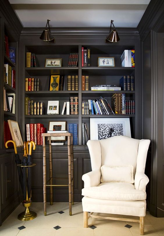 corner with dark brown bookcase, white leather chair, umbrella holder, beige tiles