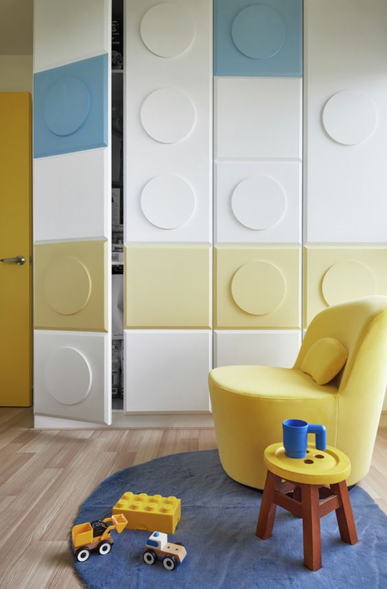 cupboard with white blue yellow color, lego style in bedroom with wooden floor, yellow chair, blue rug, low small stool