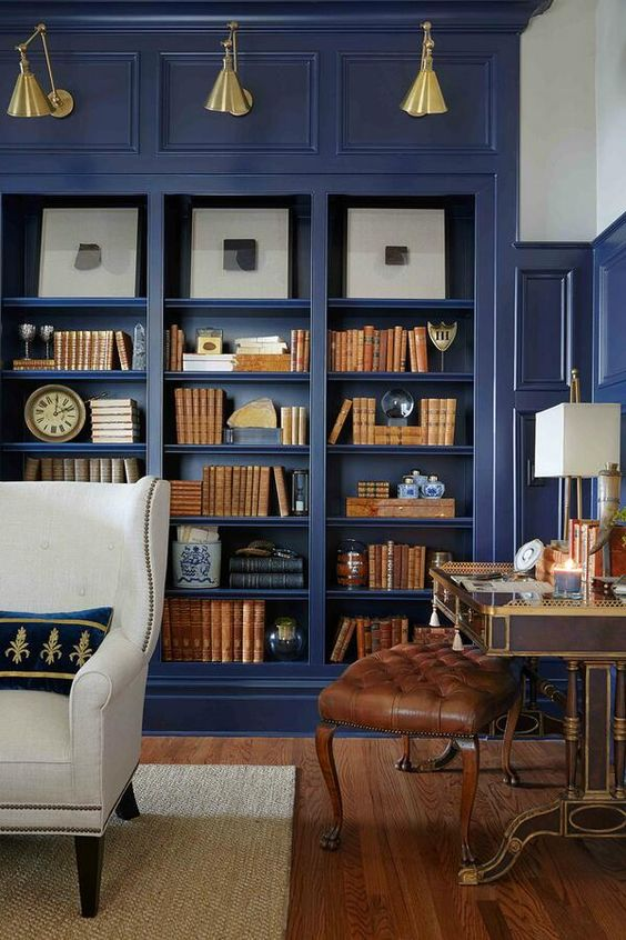 dark blue wooden bookcase, wooden floor, white leather chair, antique table, leather stool