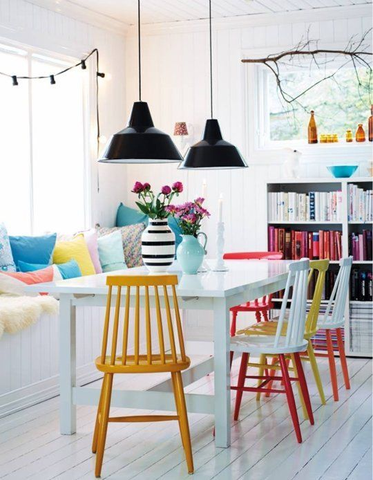dining rable set, long white wooden table, colorful wooden chairs, white wooden bench on the window colorful pillows, black pendant, white wooden floor, white shelves
