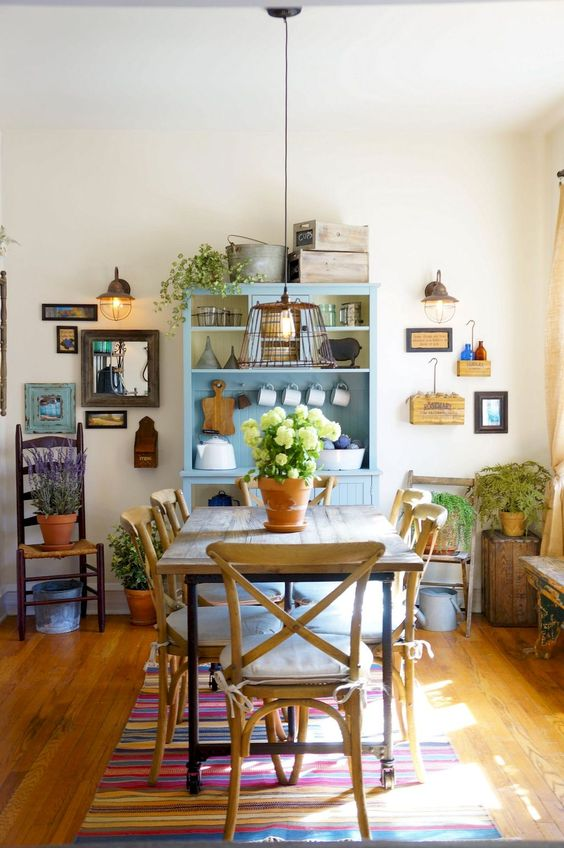 dining room, wooden floor, wooden dining table set, white wall, blue wooden shelves, wall decoration, metal cage pendant