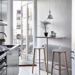 Dining Set With Table On The Wall, Thin Tall Support, Wooden Stools, White Pendant, Wooden Floor, Kitchen