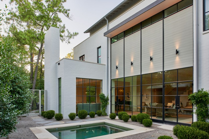exterior landscaping glass walls flat roof mini pool rocks trees chairs black modern wall sconces black framed glass doors