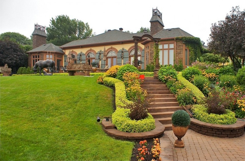 exterior landscaping grass yard stais brown pavers flowers brick walls black glass windows and doors custom bench chimney pergola outdoor chairs