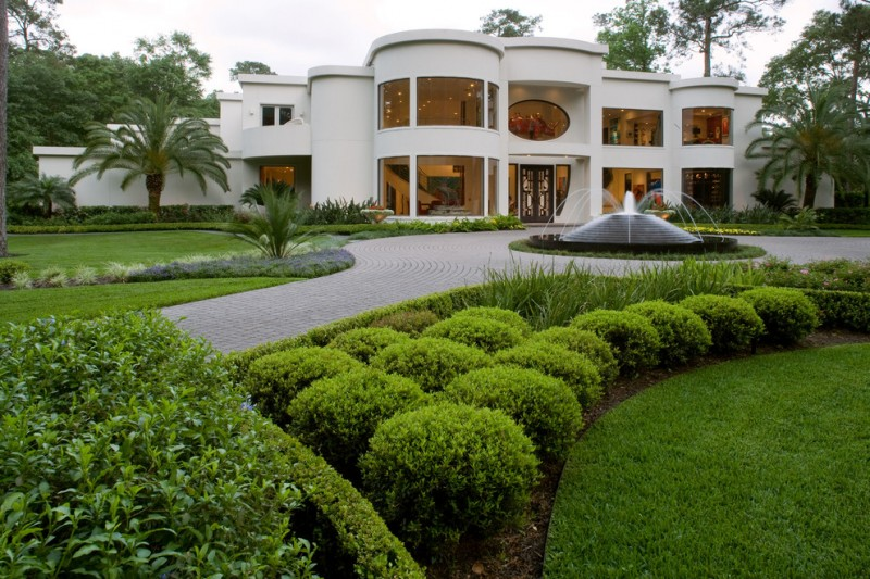 exterior landscaping green yard large white house unique fountain clear glass windows and walls artistic doors paver green balls palm tree