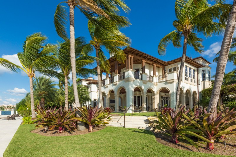 exterior landscaping trees palm tree white house concrete stairs rustic metal handrail grass pillar black glass windows doors chairs