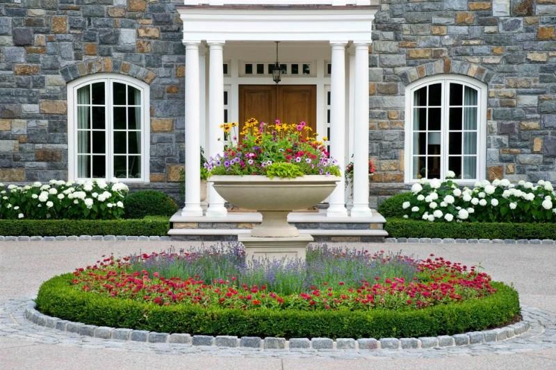 exterior landscaping wooden foor white framed glass windows stone walls small flowery garden white pillars flower fountain pendant lamp
