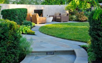 flagstone walkway design ideas grass brown and orange outdoor chairs white table glass fireplace stairs drainage plants concrete fence