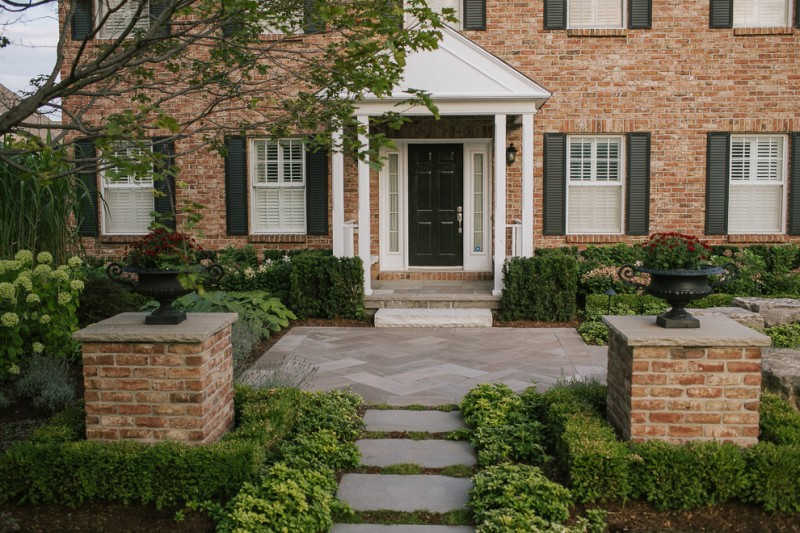 flagstone walkway design ideas herringbone stone black flower pot white pillars white windows brick house wall sconce black door
