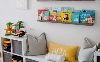 floating brown wooden shelves, white wall, wooden floor, white boxes shelves, bench, pillows,  rug,