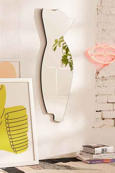 frameless body shaped mirror on white wall, open brick wall