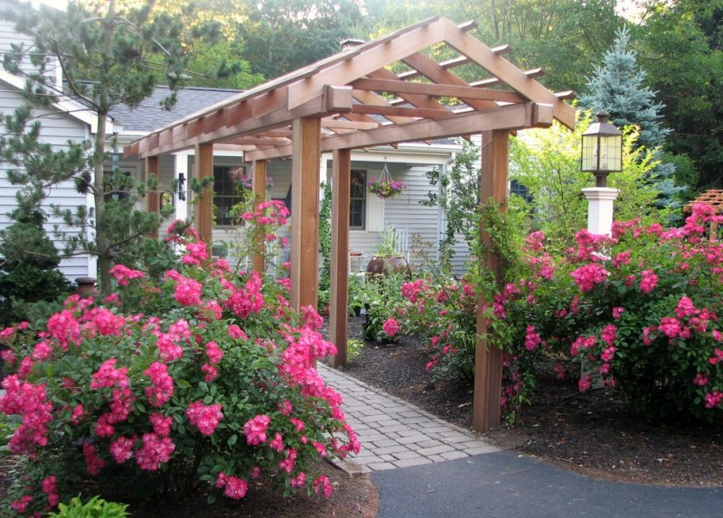 garden arbor ideas flower garden concrete and paver walk outdoor lighting grey house dark roof glass windows wall sconce