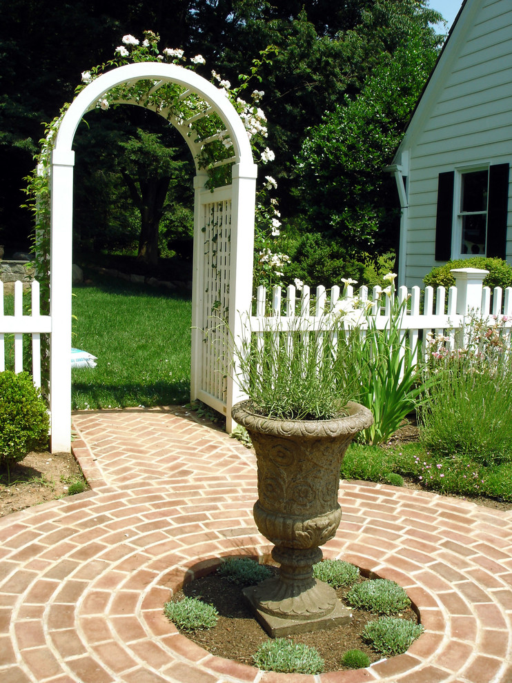 garden arbor ideas rustic fountain brick pathway white wooden arbor white wooden traditional fence white house grass white rose black glass windows