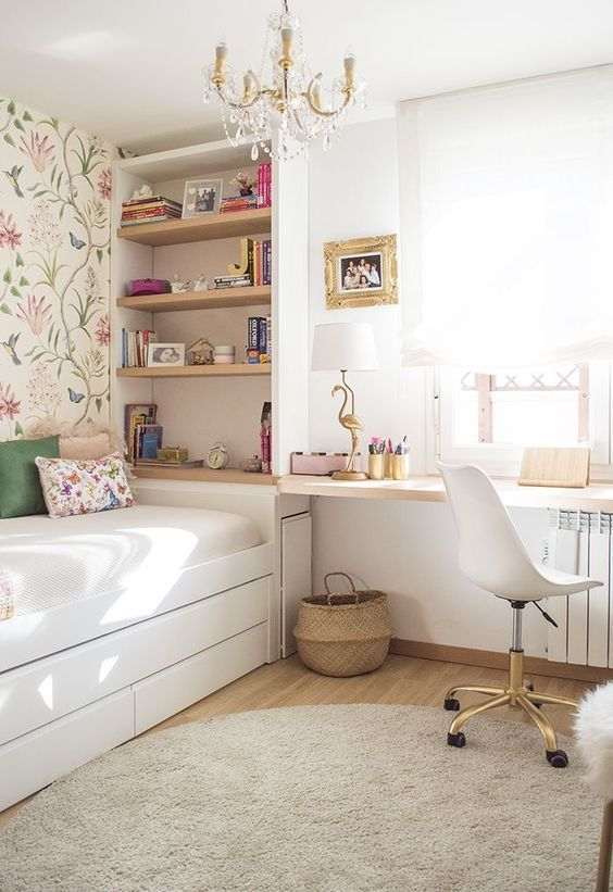 girl teen room, wooden floor, grey rug, white floating table, white modern office chair, white wooden shelves as headboard, small white bed platform, flower wallpaper, chandelier