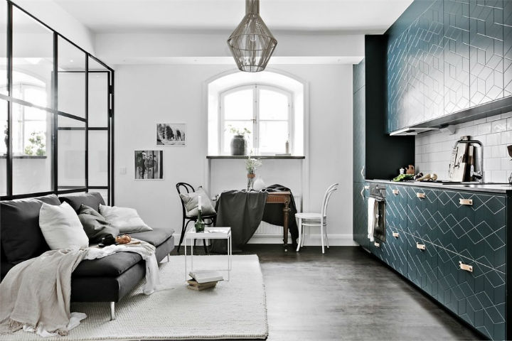 glass partition with black metal frame, door on the side end, black sofa, grey rug, dining set, kitchen, black floor, pendant