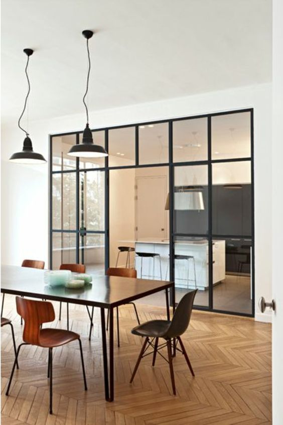 glass partition with black metal framed separating kitchen and dining area, chevron wooden floor, black table, modern chairs, modern pendant