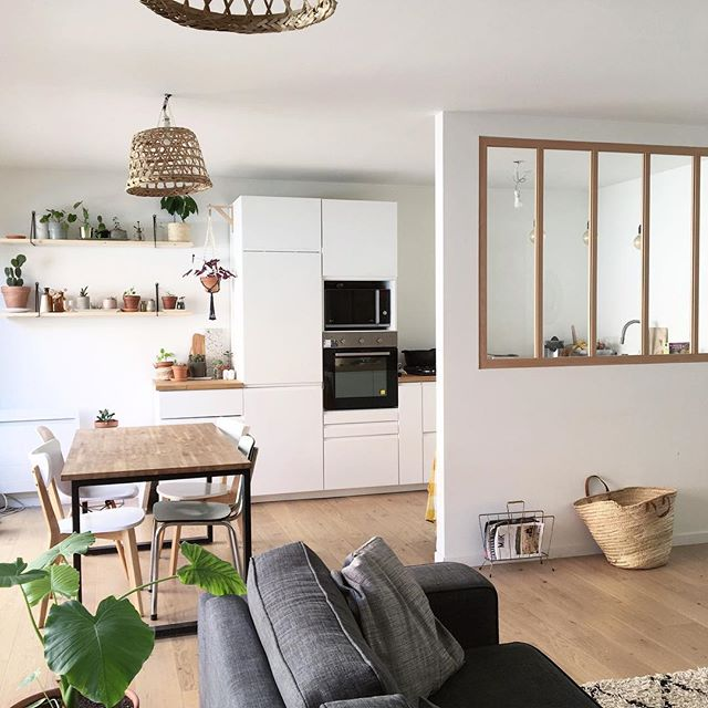 glass partition with wooden frame on white wall, kitchen with white cabinet, wooden floor, dining table set, grey sofa