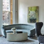 Green Cornered Curvy Sofa, Round Coffee Table With Glass Top, Blue Rug, Grey Chair, Beige Wall, Windows