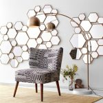 Hexagon Mirrors Scattered On The Wall, White Floor, Rattan Rug, Chair, Floor Lamp, Beige Wall