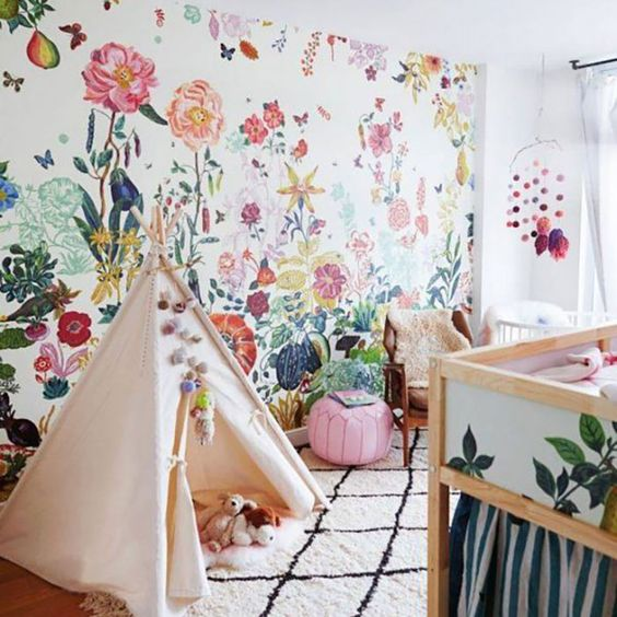 kids bedroom with wooden floor, rug, tent, colorful flower wallpaper, brown chair, white crib